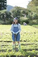 畑でスコップを持つ日本人女性