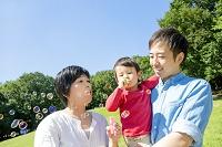 公園でシャボン玉を吹いて遊ぶ日本人家族