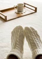 トレーにのった生姜湯と靴下をはいた足