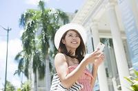 夏のリゾートでスマートフォンを使う日本人女性