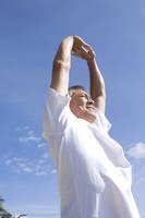空と伸びをする中高年男性