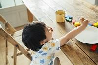 テーブルに手を伸ばす日本人の男の子