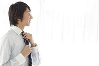 鏡を前に身支度をする日本人ビジネスマン