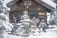 雪の中クリスマスツリーの飾りつけをする家族