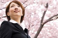 桜の下で笑顔のビジネスウーマン