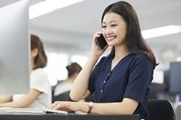 電話を受ける日本人ビジネスウーマン