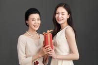 母の日に贈り物を渡す女性