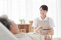 タブレットを持つ日本人女性ヘルパーとシニア