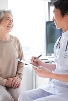医師から問診されるシニア日本人女性