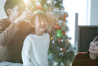 クリスマスツリーの前で微笑む日本人親子