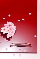 赤い漆の盆上の桜の枝、花びら、漆塗りのナイフとフォーク