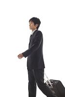 スーツケースを持って歩く日本人ビジネスマン