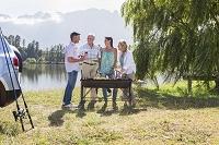 湖畔でバーベキューをする中高年の家族