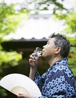 冷酒を飲む浴衣のシニアの日本人男性