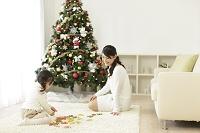 クリスマスツリーのあるリビングで遊ぶ親子