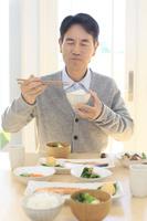 朝食を食べる中年日本人男性