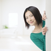 壁から顔を出して微笑む日本人女性