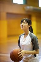 体育館でバスケットボールをする女子学生