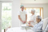 食事を手伝う介護士男性と日本人シニア夫婦
