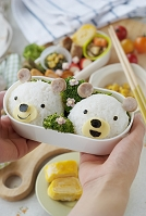 クマのキャラクター弁当を持つ女性の手元