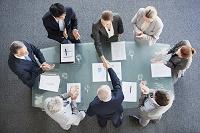 会議で握手をするビジネスチームたち