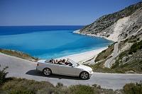 オープンカーで海岸沿いをドライブする外国人家族