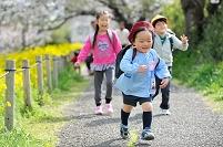 走ってくる日本人の男の子と後ろで笑っている小学生