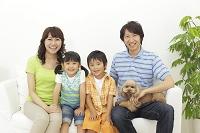 ソファーに座る家族と犬