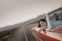 オープンカーから顔を出す笑顔の女性
