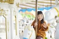 メリーゴーランドに乗る日本人の女の子