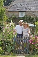 庭に立つ笑顔の外国人のシニア夫婦
