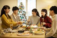クリスマスパーティーで談笑をする若者たち