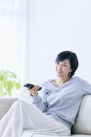リモコンを持つアラフィフの日本人女性