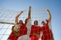 ゴール内でガッツポーズをするサッカー選手達