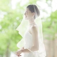 ウェディングドレスを着てベールをつけた新婦
