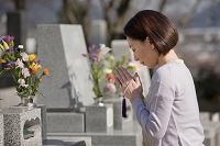 お墓の前で手を合わせる日本人女性