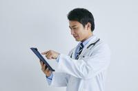 タブレットを操作する日本人医師