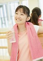 フィットネスジムで休憩する若い女性