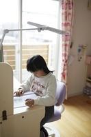 子供部屋の学習机で勉強する日本人の女の子