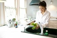 キッチンで野菜を洗う日本人女性