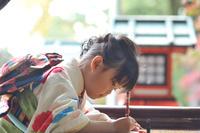 絵馬に願い事を書いている七五三の女の子