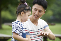 娘に虫を見せる父親