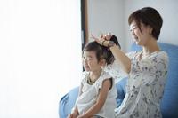 髪を結ってもらう女の子とお母さん