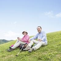 草原に座る日本人のシニア夫婦