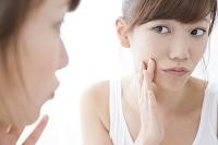 鏡を見てお肌をチェックする日本人女性
