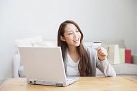 クレジットカードで楽しくネットショッピングする日本人女性