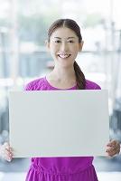 メッセージボードを持つ笑顔の女性