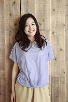 木の壁の前で微笑む若い日本人女性