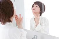 鏡を見る中高年日本人女性