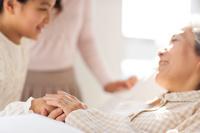 入院している祖母と手を繋ぐ孫娘